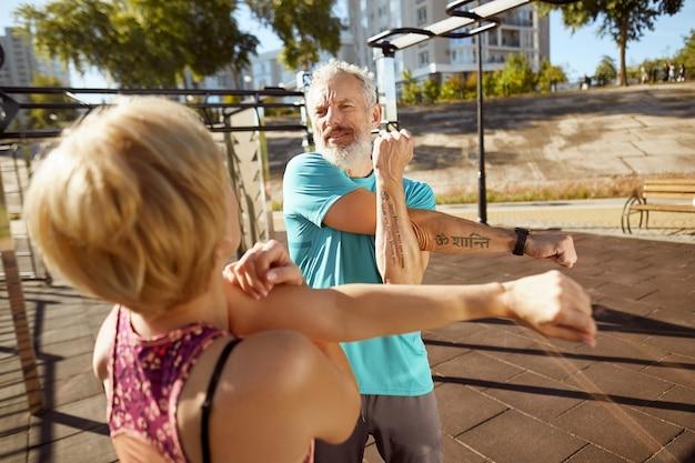 Körperlich aktiv in jedem alter sportlich reifes familienpaar in sportkleidung, das dehnübungen macht