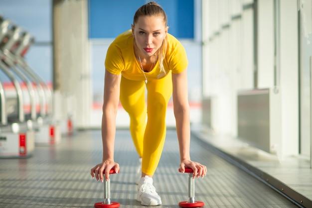 Körperlich fit frau im fitnessstudio mit hanteln bereit, ihre arme und bizeps zu stärken