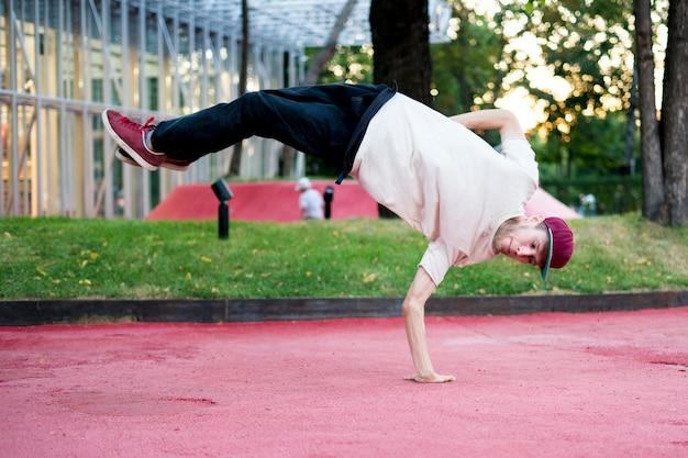 Körperliche aktivität der akrobat-freiheit des jungen mannes im städtischen stadtkonzept