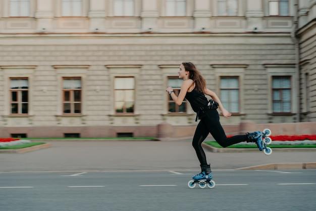 Körperliche aktivitäten im freien. gesunde junge frau hat eine schlanke figur, die einen aktiven lebensstil führt und ihre freizeit draußen auf rollerblades verbringt