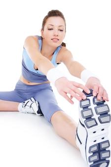 Körperliche dehnung des jungen sportlichen mädchens lokalisiert auf weiß