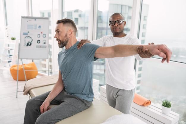 Körperliche erholung. netter professioneller therapeut, der hinter seinem patienten steht und ihm bei der therapie hilft