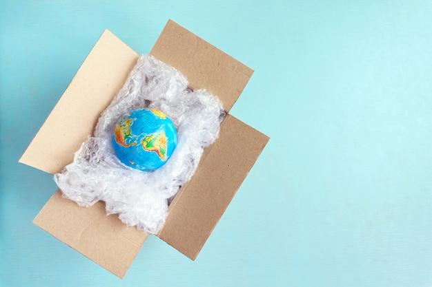 Körperliche kugel, erde in der plastikverpackung im kartonkasten auf blauem hintergrund