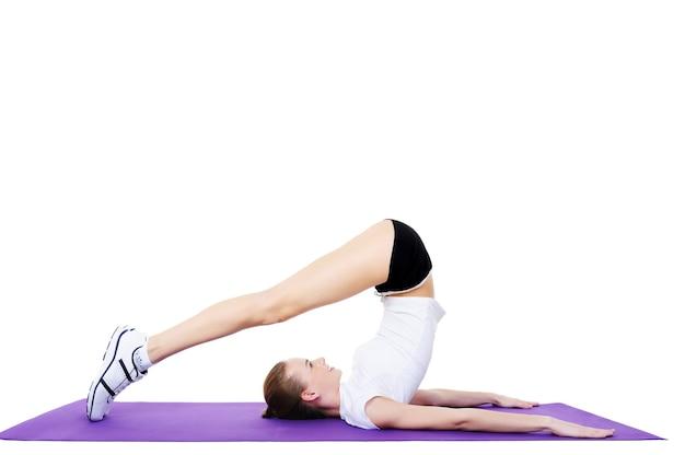 Körperliche übungen der jungen schönen frau - lokalisiert auf weiß