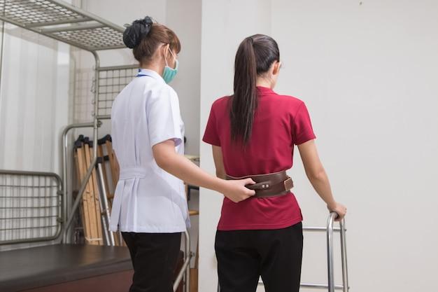 Körperlicher therapeut, der geduldigem weg mit wanderer im krankenhaus hilft
