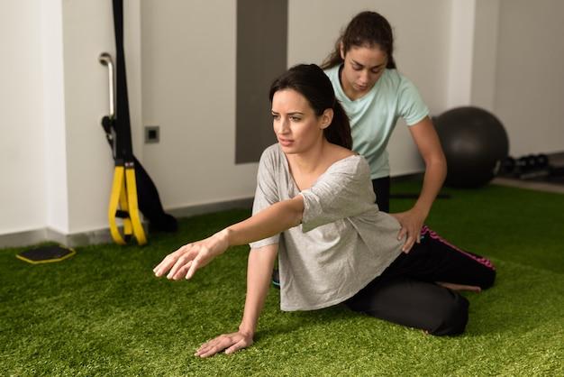 Körperlicher therapeut, der junge kaukasische frau mit übung unterstützt