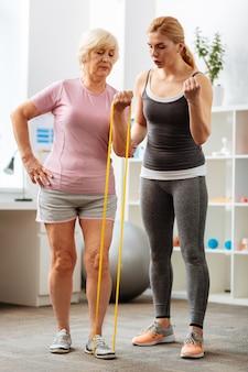 Körperliches training. nette blonde frau, die neben ihrem patienten steht und erklärt, wie man die übung macht