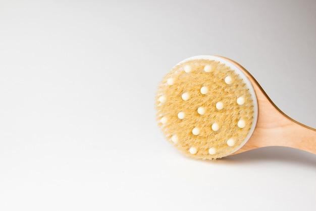 Körpermassagebürste auf grauem hintergrund. spa-massagebürste mit naturborsten für körperpeeling oder anti-cellulite-massage.