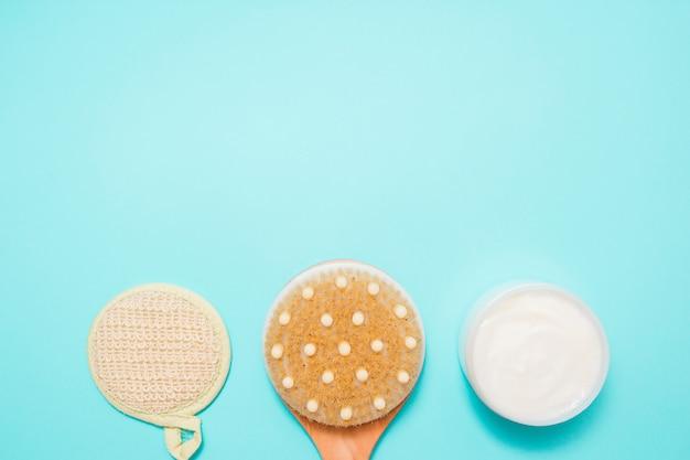 Körpermassagebürste mit sahne auf blauem hintergrund. spa-massagebürste mit naturborsten für körperpeeling oder anti-cellulite-massage. ansicht von oben.