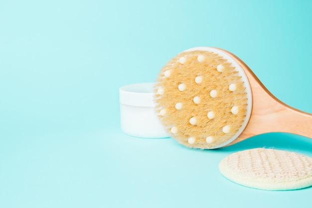 Körpermassagebürste mit sahne auf blauem hintergrund. spa-massagebürste mit naturborsten für körperpeeling oder anti-cellulite-massage.