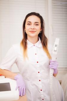 Körperpflege. ärztin, die maschine für laser-haarabbau anzeigt