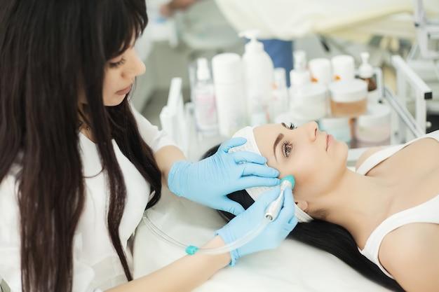 Körperpflege. frau, die gesichtshautanalyse empfängt. kosmetologie
