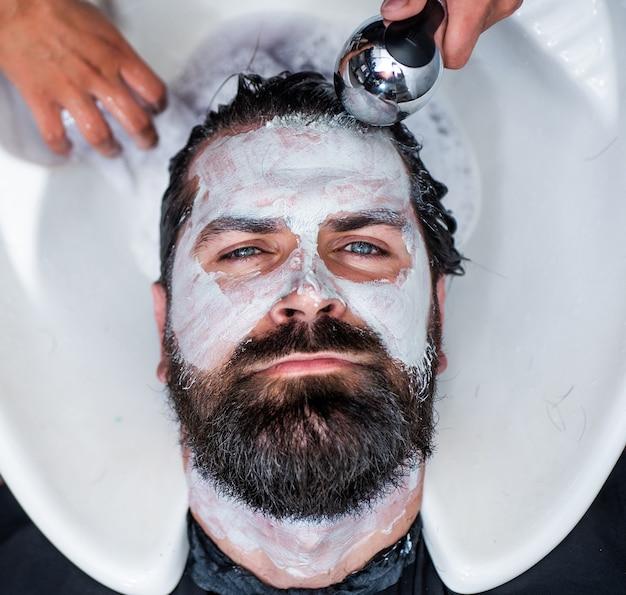 Körperpflege kosmetik. friseurmeister haare und gesichtshaare waschen. reifer hipster mit bart beim friseur. brutaler hipster mit schnurrbart haare vor der frisur waschen. friseursalon waschbecken. männliche trendige frisur.