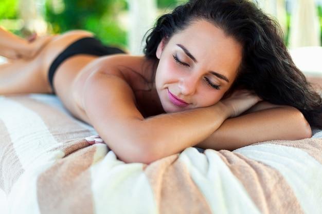 Körperpflege. spa frau. beauty-behandlungskonzept. schönes gesundes kaukasisches mädchen, das auf massagetabelle vor handmassage auf entspannter rückseite im gesundheits- und badekurortsalon sich entspannt. hautpflege, wellness, lifestyle