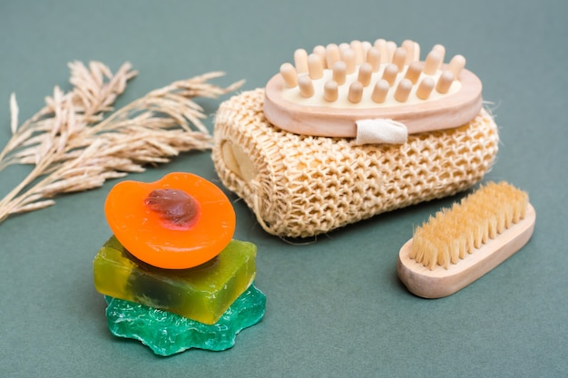 Körperpflege. verschiedene arten von handgemachter seife ohne zusatzstoffe, waschlappen, massagegerät und pinsel auf grünem grund.