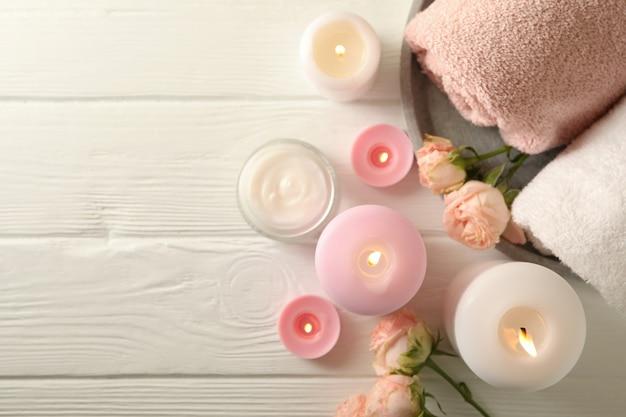 Körperpflegekonzept mit duftkerzen auf weißem holzhintergrund