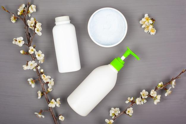Körperpflegekosmetik, weiße flaschen auf einem grauen hintergrund mit zweigen der blühenden kirsche, draufsicht.