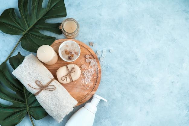 Körperpflegeprodukte auf hellblauem hintergrund mit tropischen blättern.
