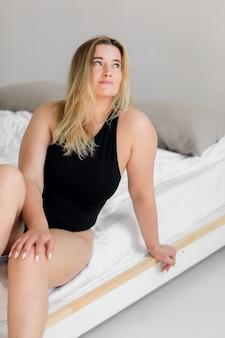 Körperpositiv posiert eine frau in schwarzer unterwäsche auf einem modernen weißen interieur
