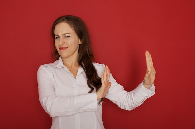 Körpersprache. angewidert gestresste wütende schöne junge frau, die an der studiowand aufwirft