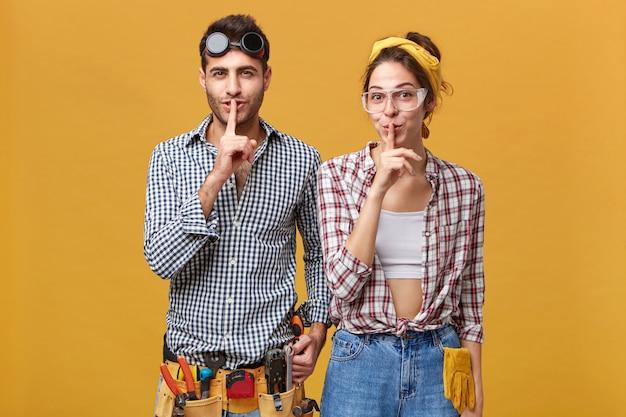 Körpersprache. attraktive männliche und weibliche elektrotechniker, die eine schutzbrille und freizeitkleidung tragen, dicht beieinander stehen, zeigefinger auf den lippen halten und um stille bitten
