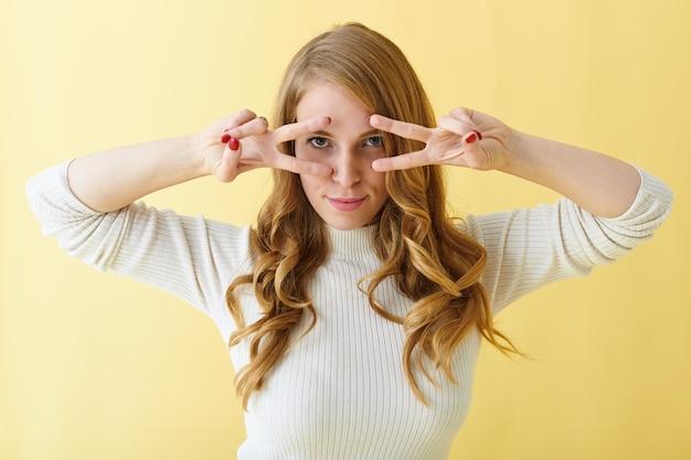 Körpersprache. horizontales porträt einer koketten verspielten jungen europäischen frau mit langer lockiger frisur, die durch ihre mittel- und zeigefinger in die kamera starrt, als ob sie mit jemandem tanzen oder flirten