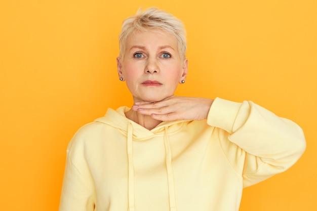 Körpersprache. horizontales studiobild der frustrierten wütenden rentnerin in stilvollem kapuzenpulli, der handfläche an ihrem hals hält, drohende geste macht, sie bedroht, müden müden blick missfallen
