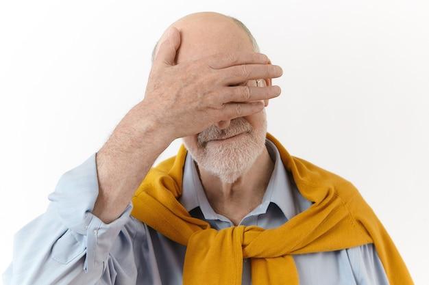 Körpersprache. isolierte ansicht des modischen eleganten älteren geschäftsmannes mit bart und kahlem kopf, der augen mit einer handfläche bedeckt, während mit seinem enkel spielt. reifer alter mann schämt sich
