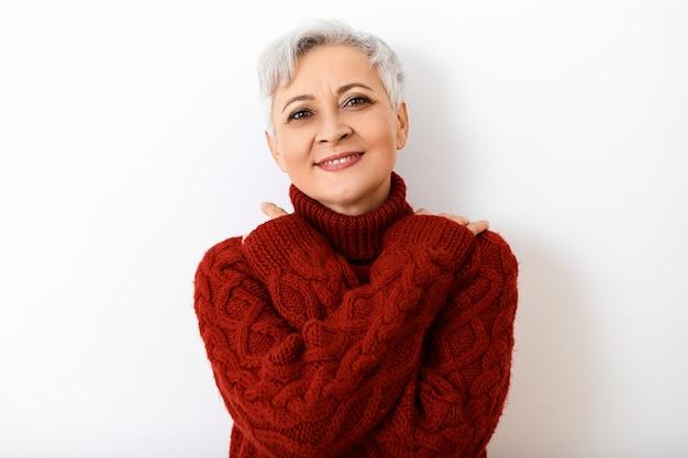Körpersprache. porträt der schönen modischen älteren europäischen frau, die sich am kalten wintertag wärmt, arme auf ihrer brust verschränkt und lächelt, gekleidet in gemütlichen burgunderfarbenen rollkragenpullover