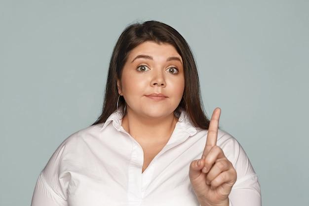 Körpersprache. strenge attraktive junge übergewichtige weibliche geschäftsführerin mit pummeligen wangen, die die augenbrauen hochziehen, unzufrieden mit ineffektiven arbeitsergebnissen sind, mitarbeiter zurechtweisen und zeigefinger schütteln