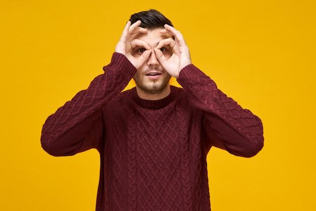 Körpersprache und menschliche mimik. fröhlicher verspielter junger mann im pullover, der daumen und vorderfinger verbindet, kreise um die augen macht, durch löcher schaut wie mit einem fernglas, spionage