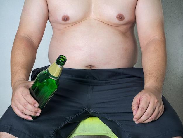 Körperteil des asiatischen fetten mannes mit einem dicken bauch, der eine flasche bier hält