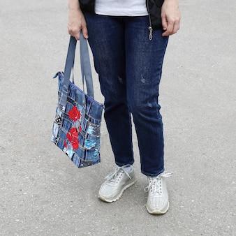 Körperteil einer frau in jeans und turnschuhen, die die tasche in den händen hält, aus denim genäht