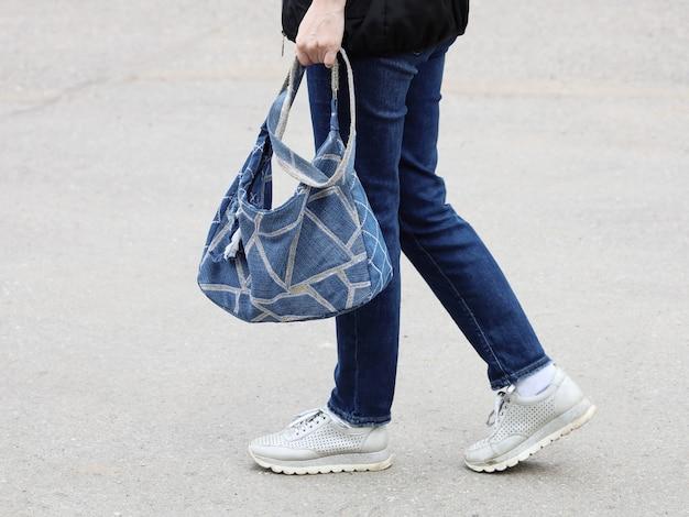 Körperteil einer frau in jeans und turnschuhen, die eine aus denim genähte tasche trägt