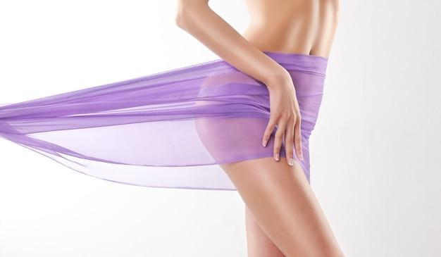 Körperteile anmutige hand auf der eleganten kurve der hüfte, die von lila tuch bedeckt ist schönheit des frauenkörpers