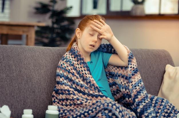 Körpertemperatur. blasses rothaariges mädchen, das ihre stirn berührt, während es unter hoher temperatur leidet