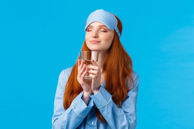 Köstlich. erfreute und zufriedene niedliche glamouröse rothaarige kaukasische frau in schlafmaske und nachtwäsche trinken erfrischendes und leckeres getränk, glaswasser mit geschlossenen augen und lächeln haltend, blaue wand