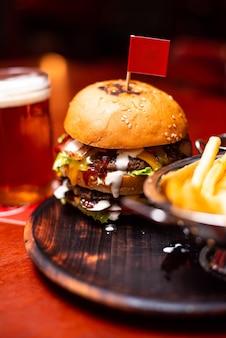 Köstlich lecker gegrillter hausgemachter burger mit rindfleisch, käse, speck und sauce auf holztisch mit kopierraum. hände, die burger mit pommes frites und bier halten gruppe von freunden, die fastfood essen