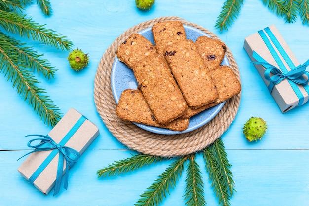 Köstlich zubereitete kekse für weihnachten neben geschenken und tannenzapfen.