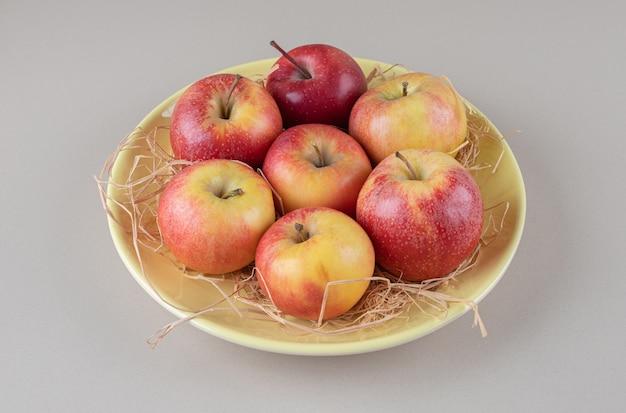 Köstliche äpfel und stroh in einer schüssel auf marmor