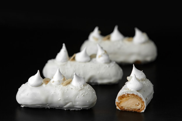 Köstliche appetitliche kuchen mit weißer schokoladencreme und kokosnuss auf einem schwarzen hintergrund