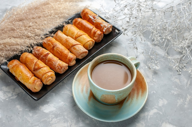 Köstliche armreifen mit milchkaffee auf hellem schreibtisch, gebäckzucker süßer backkuchen