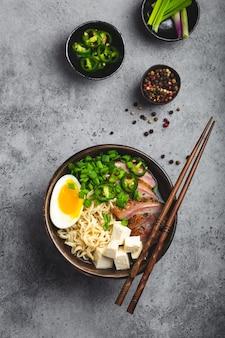 Köstliche asiatische nudelsuppe ramen in schüssel mit fleischbrühe, tofu, geschnittenem schweinefleisch, ei mit eigelb, grauer rustikaler betonhintergrund, nahaufnahme, draufsicht. heiße leckere japanische ramen-suppe zum abendessen nach asiatischer art