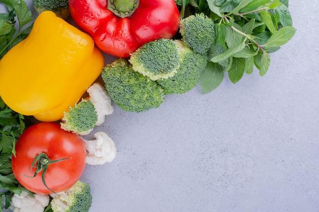 Köstliche auswahl an gemüse und grüns auf marmorhintergrund. foto in hoher qualität