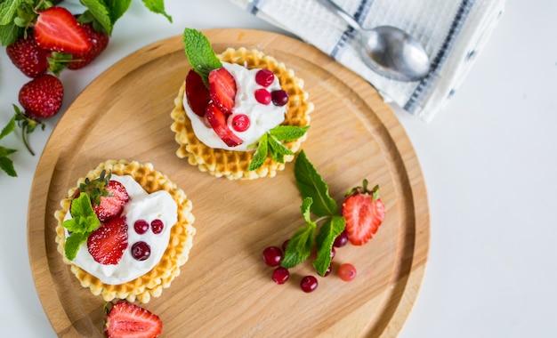 Köstliche belgische waffeln mit schlagsahne und erdbeeren auf obenliegender ebenenlage der runden hölzernen platte