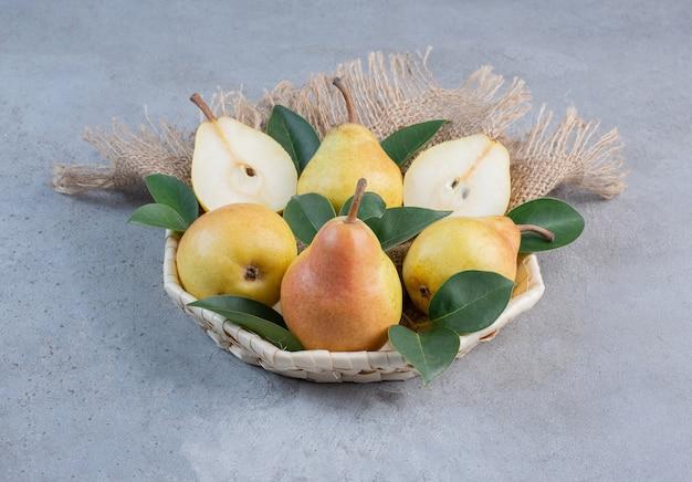 Köstliche birnen und dekorative blätter in einem kleinen korb auf marmorhintergrund.