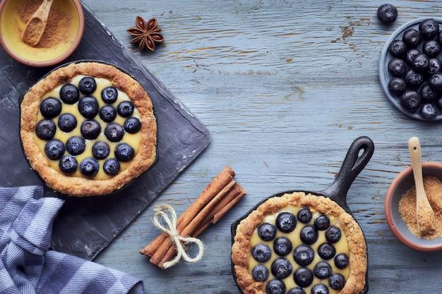 Köstliche blaubeertörtchen mit vanillepuddingcreme auf hellem rustikalem holztisch