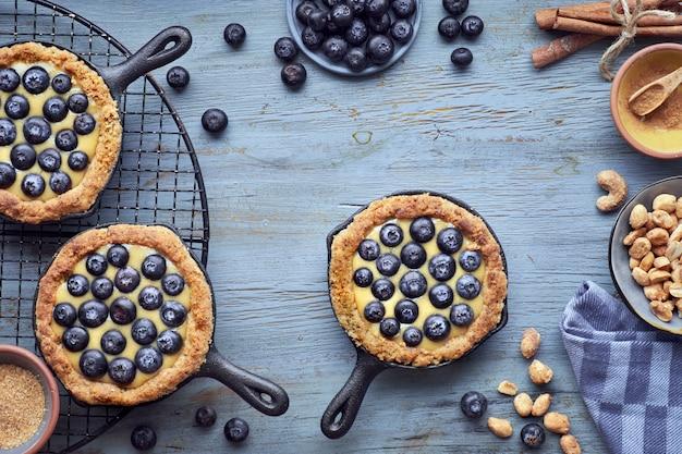 Köstliche blaubeertörtchen mit vanillepuddingcreme auf holz