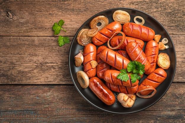 Köstliche bratwürste mit knoblauch und zwiebeln auf natürlichem holzhintergrund. fastfood.