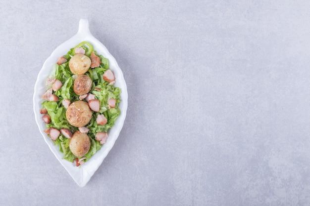 Köstliche bratwürste und salat in weißer schüssel.